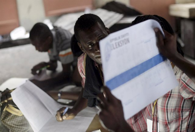 An electoral worker holds up a ballot for scrutiny during vote counting in Port-