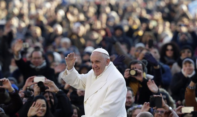 Pope Francis waves as he arrives to lead the weekly audience in Saint Peter's Sq