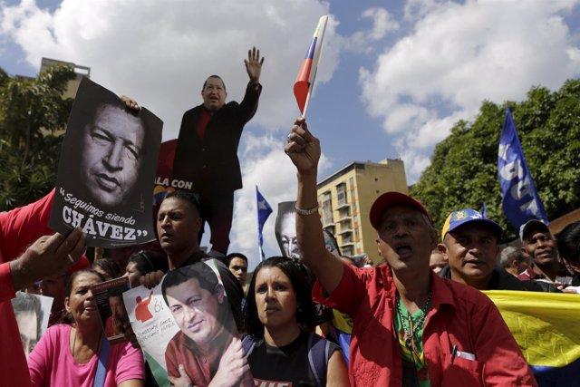 Supporters of Venezuela's President Nicolas Maduro hold up photographs of Venezu