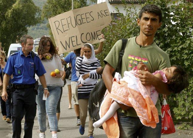 Un agente de Policía suizo acompaña a refugiados sirios