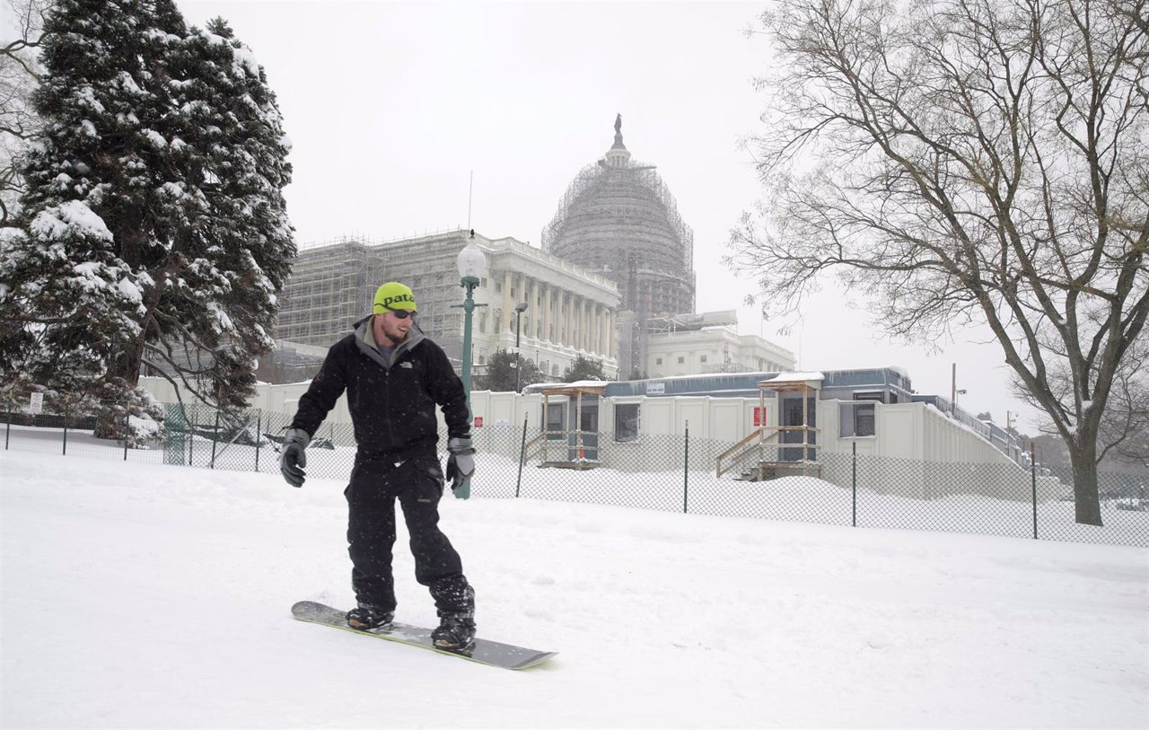 A man snowboards past the U.S. Capitol during a winter storm in Washington
