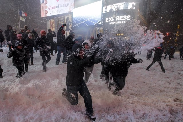 Dozens of people take part in an impromptu snow ball fight during a snow storm i