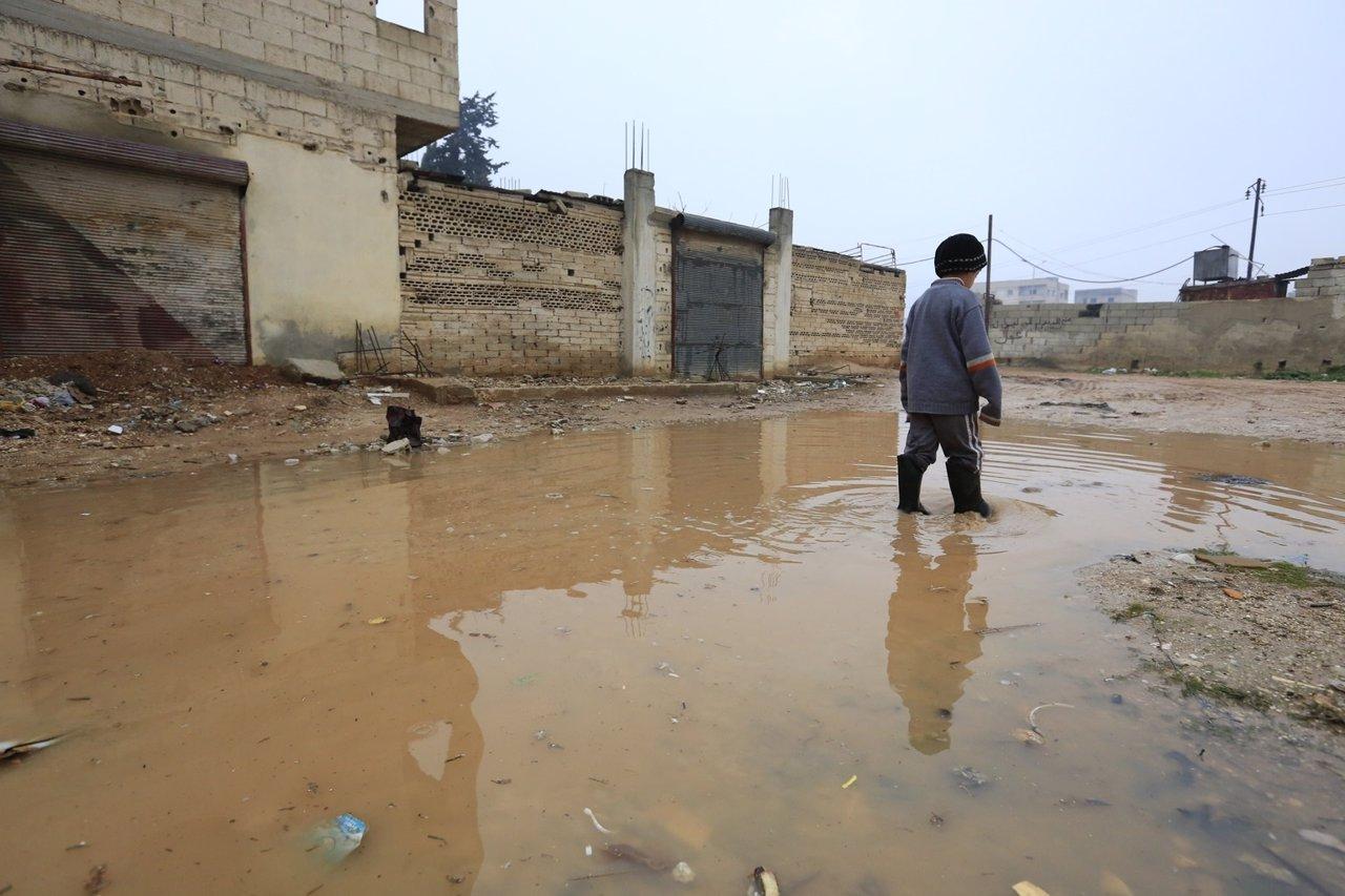 Un niño camina entre charcos en un campamento de desplazados de Homs (Siria)