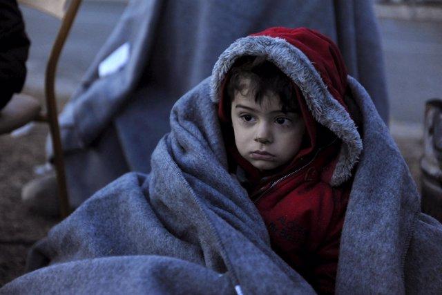 Un niño migrante cubierto con una manta cerca del pueblo griego de Idomeni