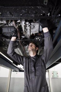 Mecanico repara un coche.