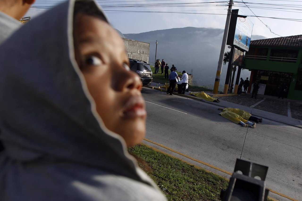 A child looks up while standing near a crime scene in Tegucigalpa