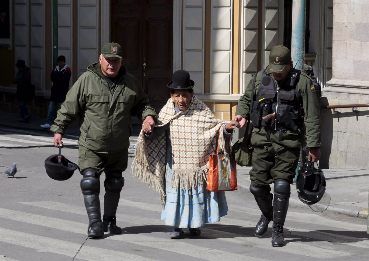 Riot police officers help an elderly woman at Murillo square during a protest by
