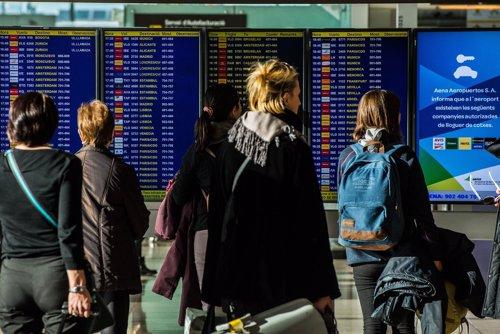 Gente mirando los paneles del aeropuerto