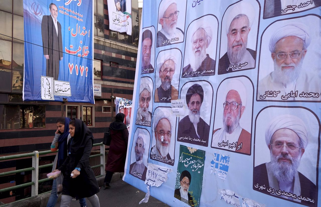 Mujeres junto a un cartel electoral en Teherán