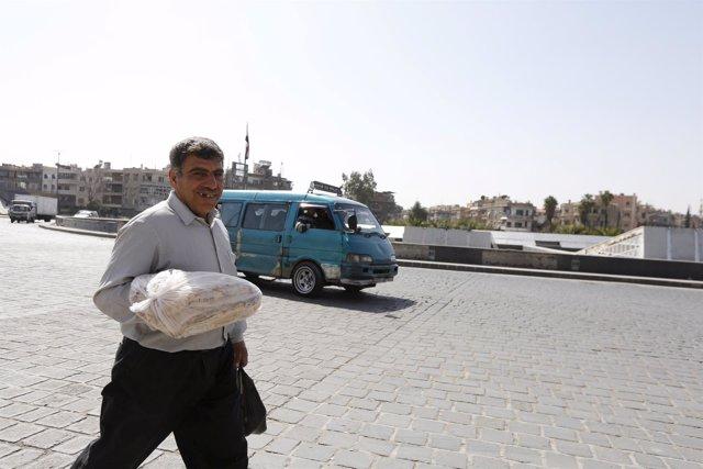 Ciudadano sirio lleva una barra de pan