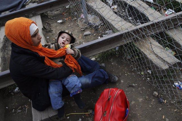 Una inmigrante y su hijo esperan en Idomeni (Grecia) a cruzar a Macedonia