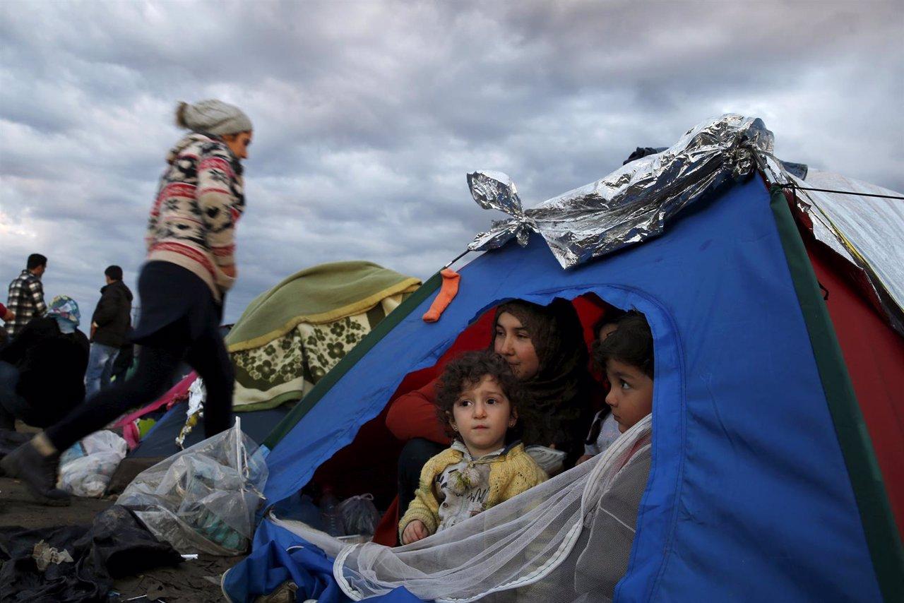 Familia de refugiados espera en una tienda de campaña en Idomeni (Grecia)