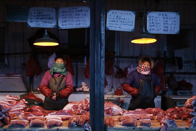 Pork vendors wait for customers at a market in Beijing