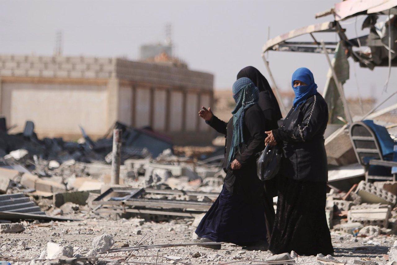 Mujeres caminan entre escombros en la provincia de Hasaka (Siria)