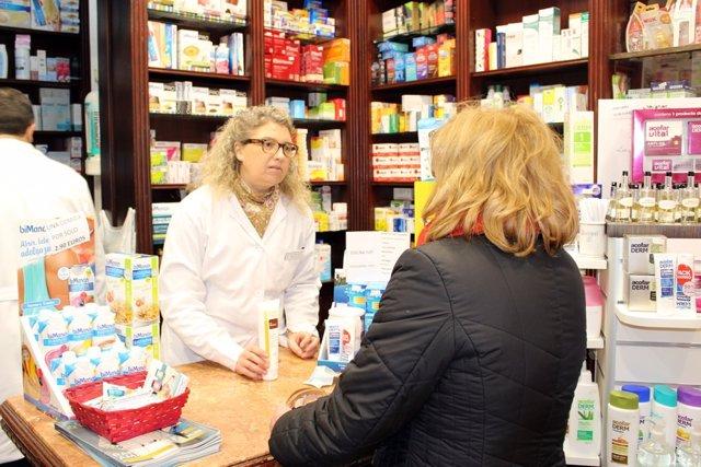 Una farmacéutica atiende a una paciente en una oficina de farmacia de Jaén.