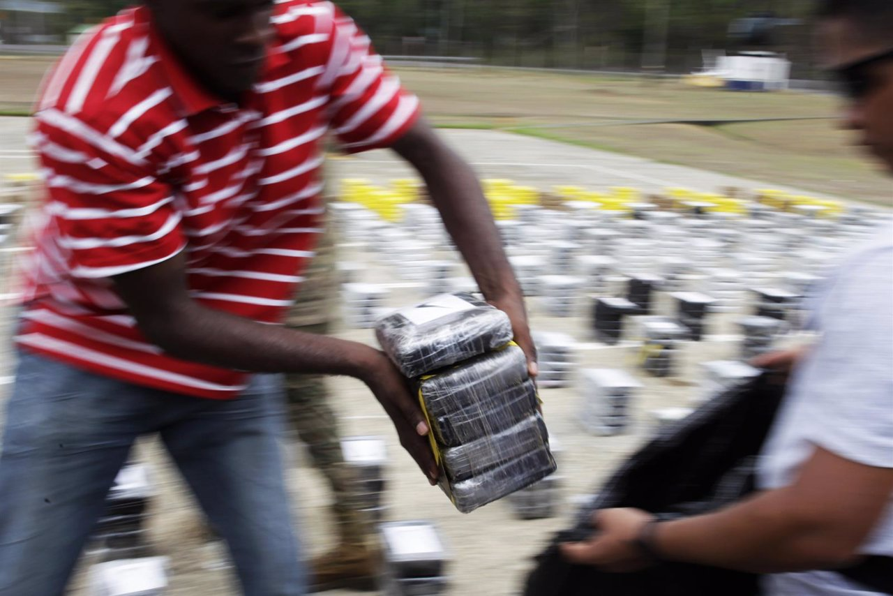 A member of the Aero Naval police carries packages of seized cocaine during a dr