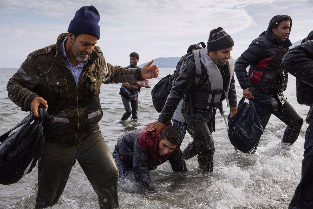 Refugiados desembarcando de una lancha en la costa de Lesbos (Grecia)