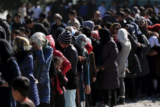 Refugiados esperan a recibir ayuda en un centro cerca de Atenas