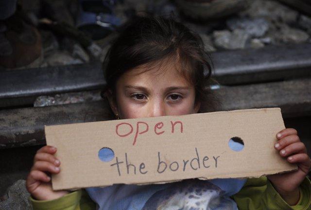 Niña refugiada muestra un cartel pidiendo la apertura de la frontera