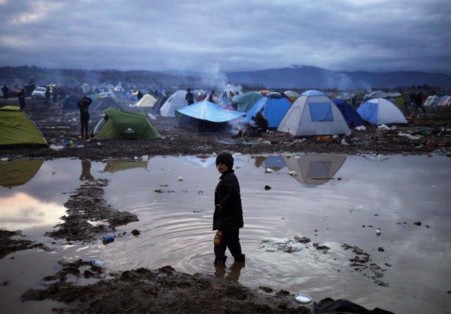 Un niño inmigrante en medio de un charco en Idomeni