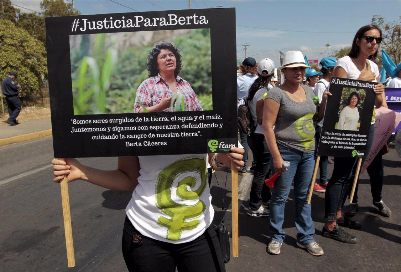 An activist holds a photos of slain environmental rights activist Berta Caceres