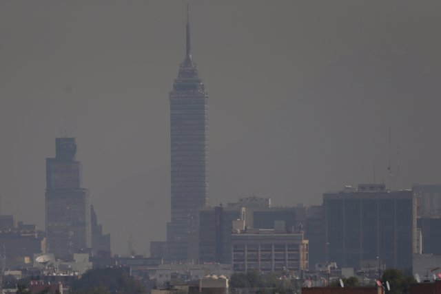 Buildings stand shrouded in smog in Mexico City