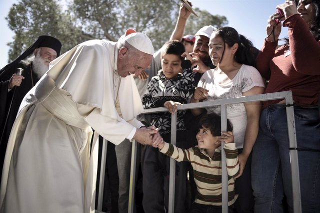 Handout photo of a boy shaking the hand of Pope Francis as he greets migrants an