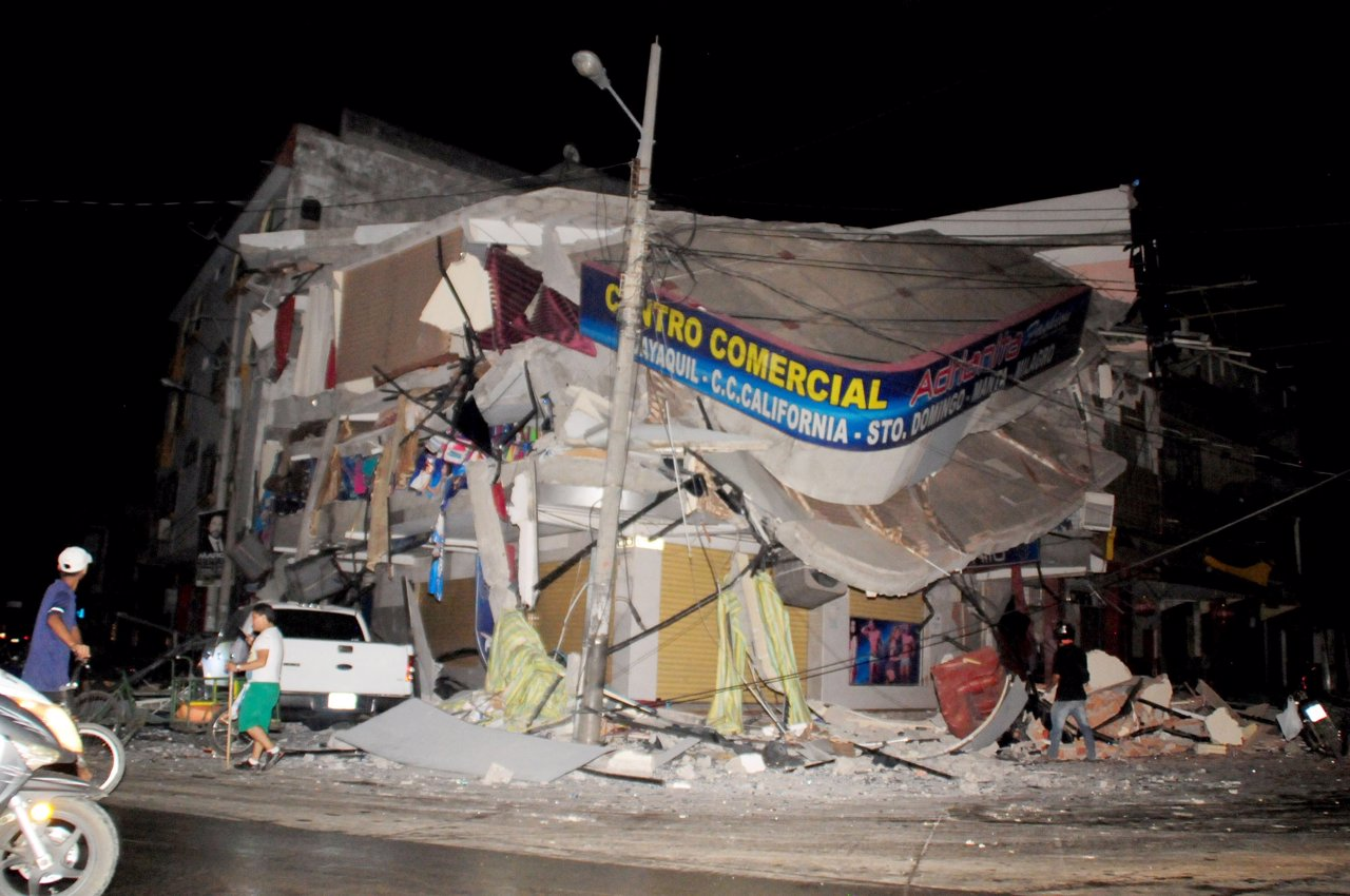People walk near a damaged house after an earthquake struck off the Pacific coas
