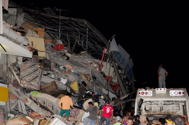 People stand next to the debris of a building after an earthquake struck off the