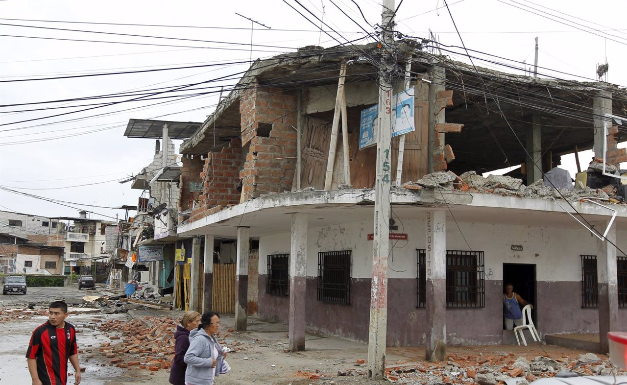 People walk by damaged buildings after an earthquake struck off Ecuador's Pacifi
