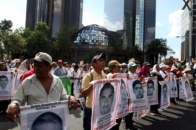 Relatives carry photos of some of the 43 missing students of the Ayotzinapa teac