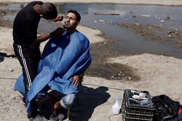 Un refugiado le corta el pelo a otro en Idomeni