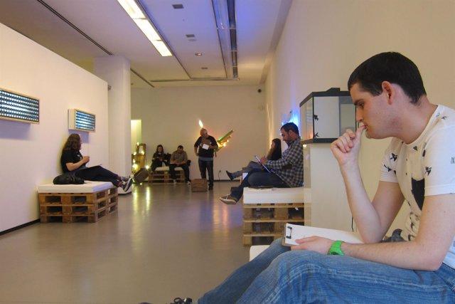 Participantes escuchan la lectura del tema de los microrrelatos.
