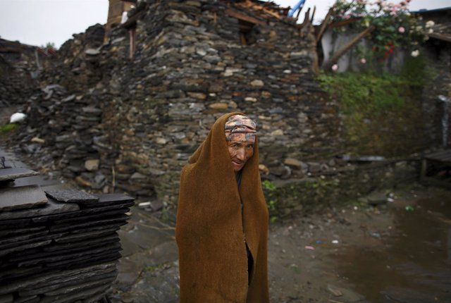 Ghale covers himself with a cloth as he walks towards his collapsed house in Bar
