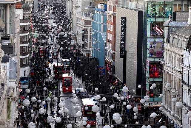 Shoppers and traffic travel along Oxford Street in London, Britain