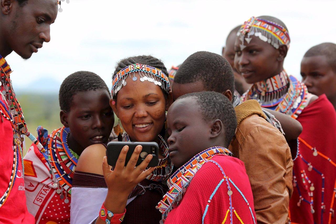 Una chica Maasai mira un vídeo en un teléfono móvil