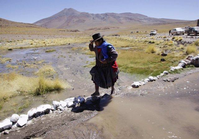Una mujer curza el río Silala en la frontera entre Chile y Bolivia