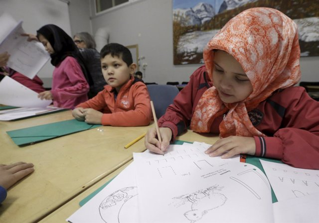 Refugee children attend class in a camp at a hotel touted as the world's most no