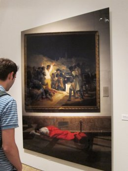 Espectador ante una foto de Eugenio Ampudia en muestra Ni cautivos ni desarmados