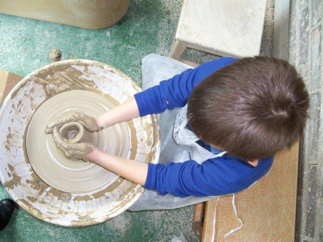 Niño creando su pieza de cerámica en el Taller Escuela de Cerámica de Muel