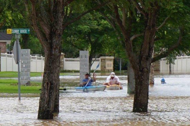 Personas en barca por las inundaciones en Estados Unidos