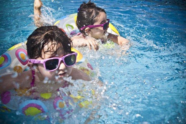 Niñas en la piscina con gafas de sol