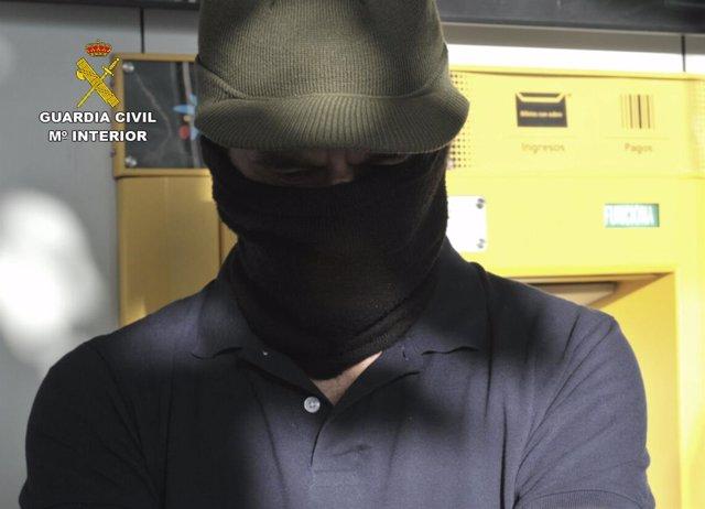 Uno de los arrestados realizando el reintegro de efectivo de un cajero