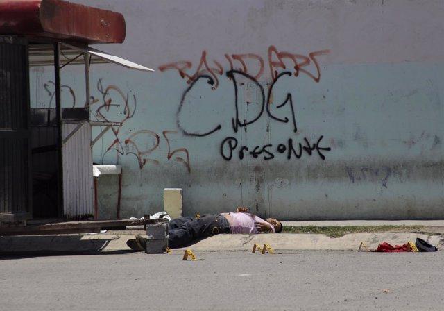 Un cadáver bajo un grafiti con las iniciales del Cártel del Golfo