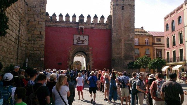 Turistas esperan este miércoles, a las puertas del Alcazar de Sevilla.