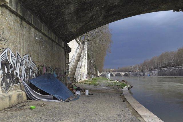 Un sin techo bajo un puente en Roma