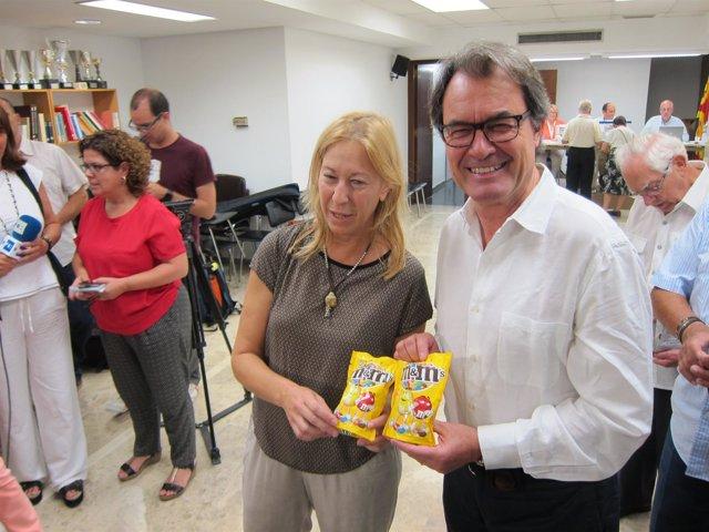 Neus Munté y Artur Mas (PDC) sostienen dos paquetes de M&M's