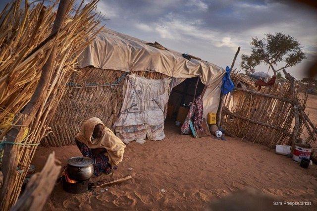 Una mujer africana cocina sobre la arena junto a su chamizo