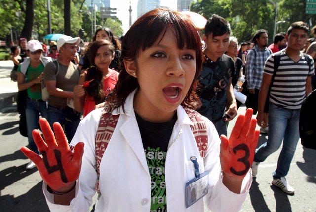 Un manifestante, con un 4 y un 3 marcha por las calles de México DF