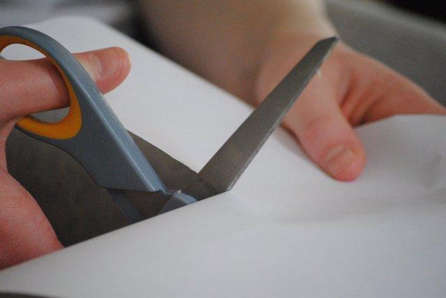 Manos cortando papel con tijeras.